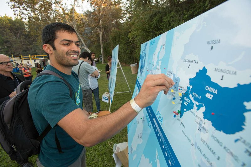 Student placing a pin on a map to indicate home country at the Welcome BBQ