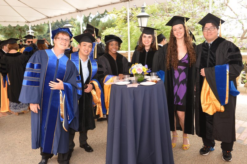Students in group pose under a tent with caps and gowns