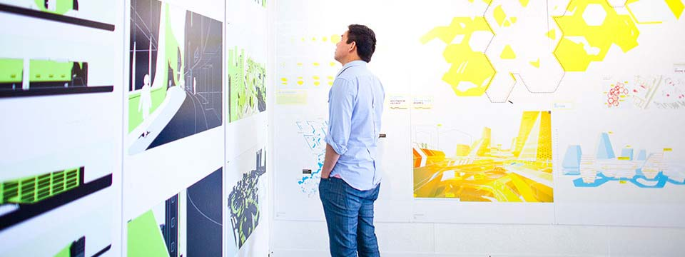 A man looks at layouts in an architecture gallery
