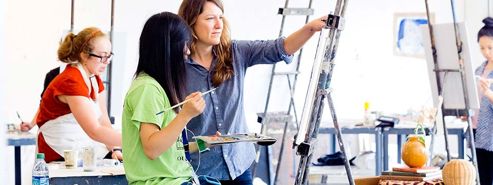 With the guidance of an instructor, a student creates art by painting on an easel