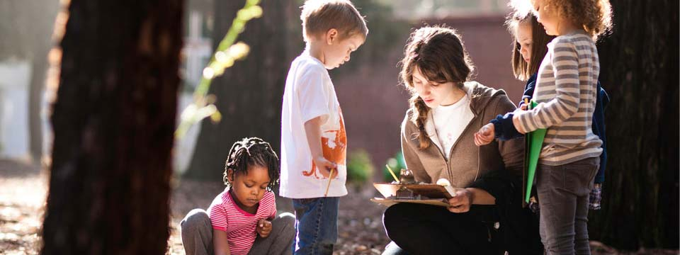A teacher holds a clipboard near her young students in a forest