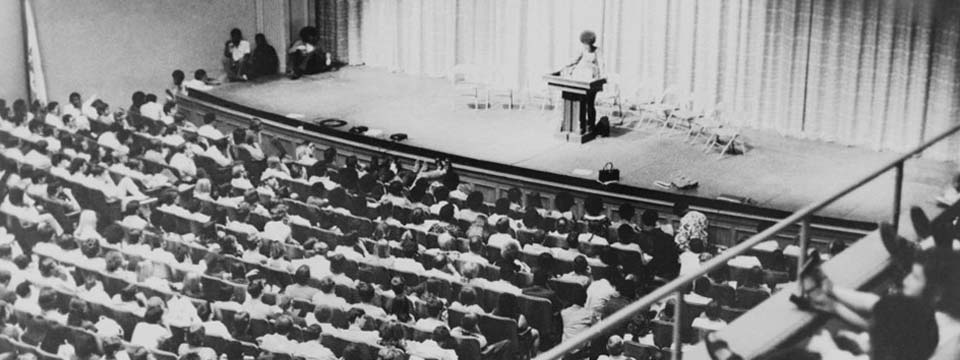 Black-and-white image of Angela Davis giving a lecture to a filled hall