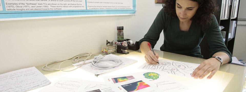 A climate scientist draws a diagram at her desk