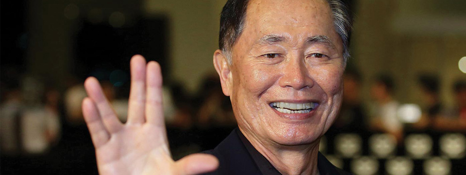 George Takei, UCLA '60, M.A. '64, holds up the the Vulcan salute