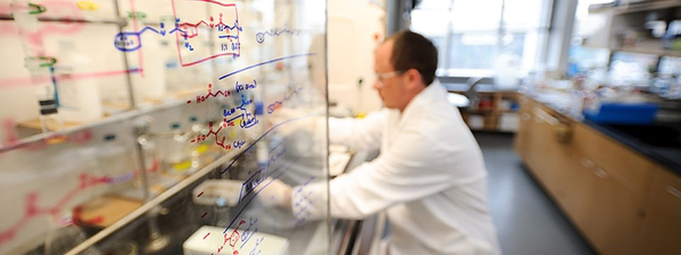 A person wearing a white lab coat, goggles, and gloves works in a lab behind a glass wall with biochemistry equations written on it
