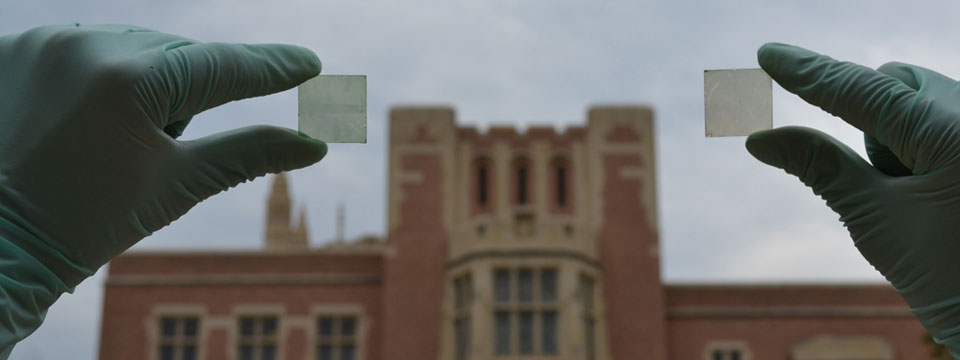 A person with gloves holds two solar cells in front of a building at UCLA