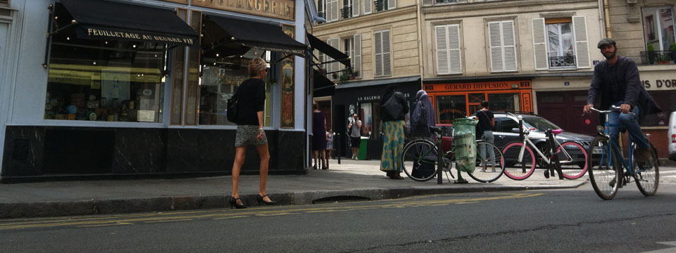 Biking past a bakery in Paris, France