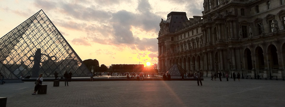 The sun sets in front of the Louvre Pyramid, a glass pyramid in Paris