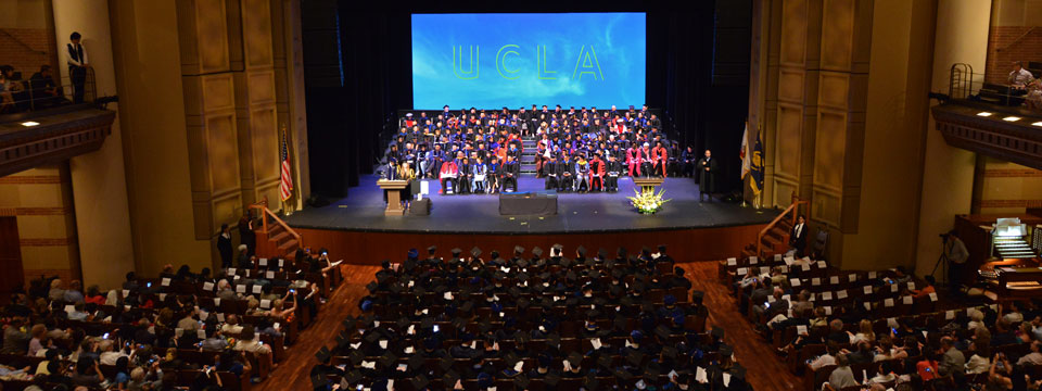 Professors sit on the stage at UCLA's graduation ceremony in Royce Hall