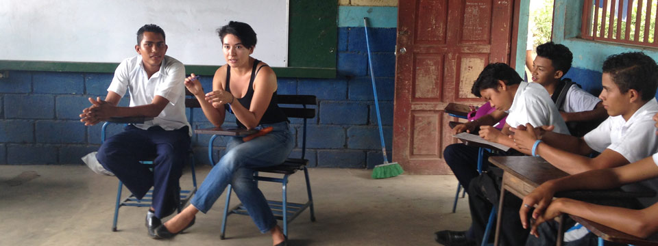 A woman leads the conversation in a classroom in Latin America