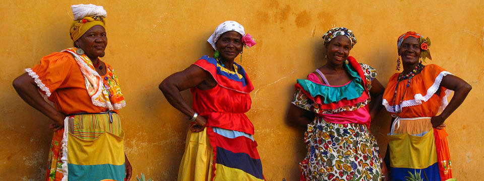 Colombian women in bright dresses and scarves, in front of a yellow wall