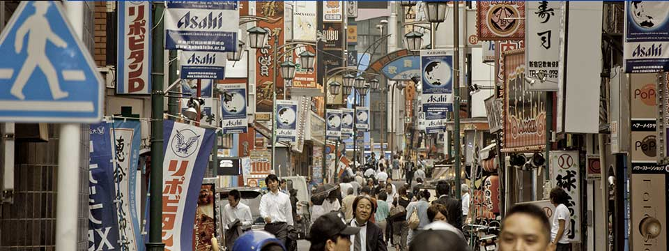 A busy city scene of Japan, with pedestrians, billboards, and signs